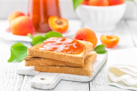 살구 잼와 신선한 과일과 빵의 토스트 흰색 나무 테이블에 나뭇잎. 맛있는 아침 식사.