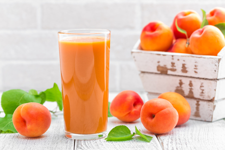 Apricot juice and fresh fruits with leaves Reklamní fotografie