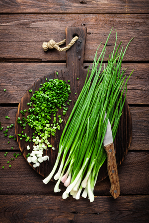 Green onion or scallion on wooden board, fresh spring chives