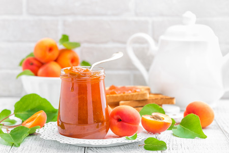 Apricot jam in a jar and fresh fruits with leaves on white wooden table, breakfast Stock Photo
