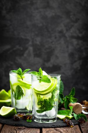 ラム酒とライム、冷たいドリンクや黒い背景に氷を飲料とさわやかなミント カクテル モヒート