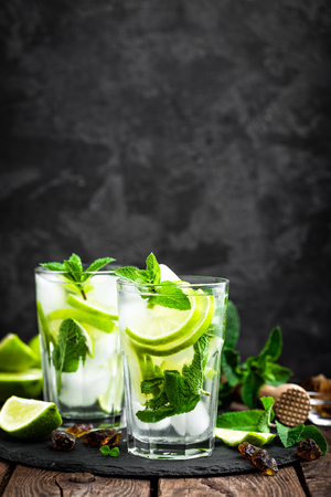 Refreshing mint cocktail mojito with rum and lime, cold drink or beverage with ice on black background Reklamní fotografie