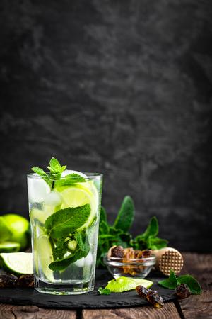상쾌한 민트 칵테일 모 히 토 럼 및 라임, 차가운 음료 또는 검정색 배경에 얼음 음료