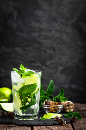 Refreshing mint cocktail mojito with rum and lime, cold drink or beverage with ice on black background Standard-Bild