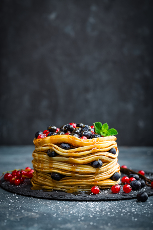 Pancakes with fresh berries and maple syrup on dark background, closeup Foto de archivo