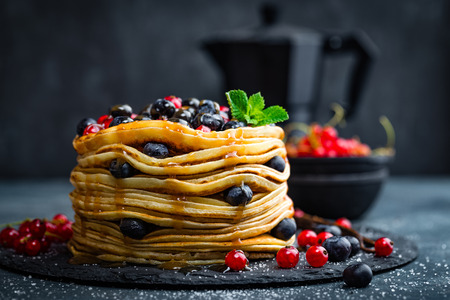 hotcakes: Pancakes with fresh berries and maple syrup on dark background, closeup Stock Photo