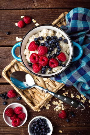 Oatmeal porridge with fresh berries, oats with blueberry and raspberry Фото со стока