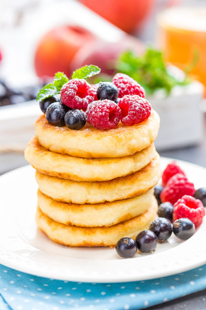 Cottage cheese pancakes, syrniki, curd fritters with berries Stock Photo