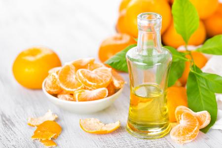 Mandarines avec des feuilles et une bouteille d'huile essentielle d'agrumes sur fond blanc