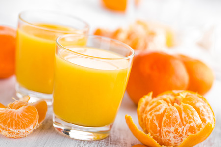 Tangerines, peeled tangerines and tangerine juice in glass. Mandarine juice. Stock Photo