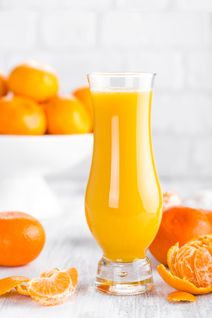 Tangerines, peeled tangerines and tangerine juice in glass. Mandarine juice. Stock fotó