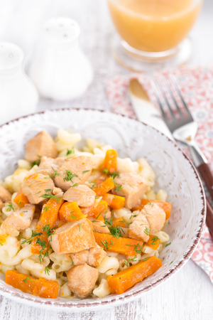 Braised chicken meat with carrot in sauce and pasta