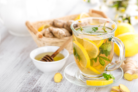 Flavored herbal tea with fresh lemon, ginger and mint leaves on white background, closeup