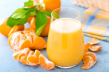 Mandarijnen, gepelde mandarijnen en mandarijnsap in glas. Mandarijnsap en vers fruit met bladeren. Stockfoto