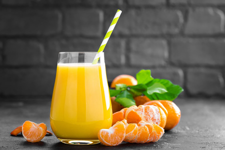 Tangerines, peeled tangerines and tangerine juice in glass. Mandarine juice and fresh fruits with leaves.
