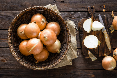 Fresh onion in basket on wooden table, top view