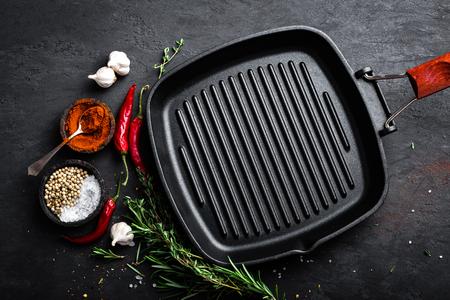黒い背景、上面に料理の食材を空の鋳鉄製のグリル鍋
