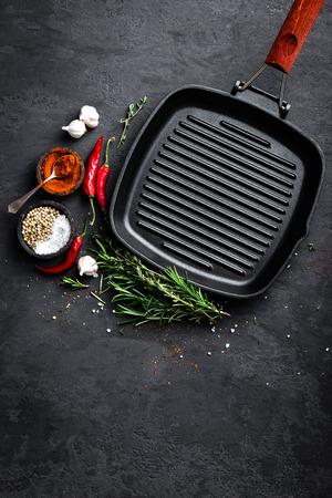 黒い背景、トップビューで調理するための食材を備えた空の鋳鉄グリルパン