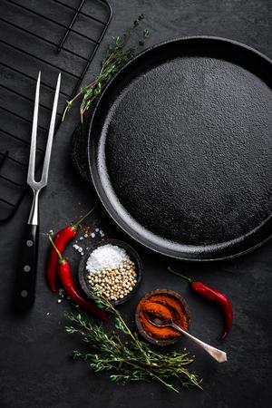 Lege gietijzerpan met ingrediënten voor het koken op zwarte achtergrond, hoogste mening Stockfoto