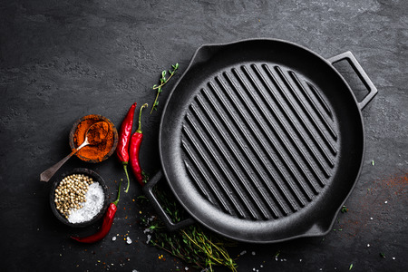 Empty cast-iron grill pan with ingredients for cooking on black background, top view Фото со стока - 91475892