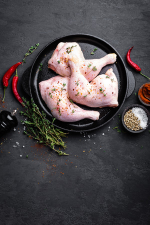 Raw chicken quarters, legs in a pan on a dark background. Top view. 스톡 콘텐츠