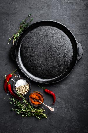 黒い背景、トップビューで調理するための成分を持つ空の鋳鉄鍋