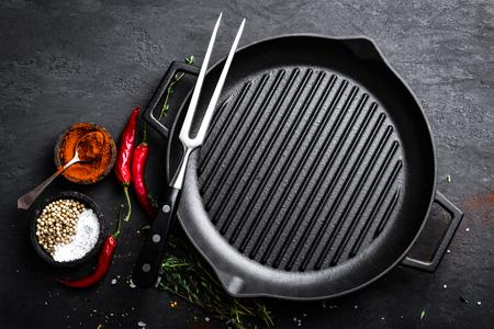 Lege gietijzeren grillpan met ingrediënten voor het koken op zwarte achtergrond, hoogste mening