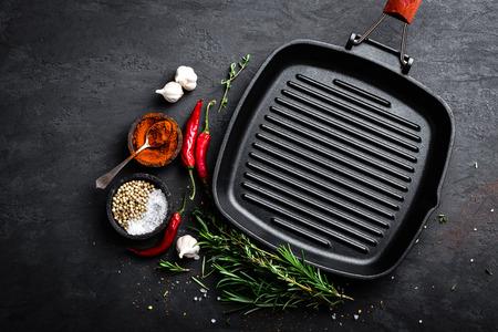 Cacerola vacía de la parrilla del arrabio con los ingredientes para cocinar en el fondo negro, visión superior