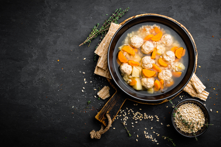 Fresh vegetable soup with meatballs and pearl barley in bowl on black background. Top view