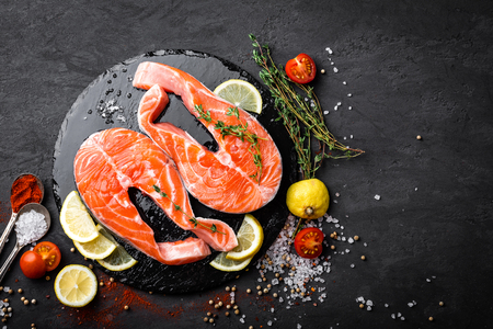 Fresh raw salmon red fish steaks on black background, top view Stock Photo