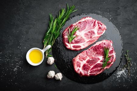 Cooking on kitchen table fresh raw pork marbled steaks on black background, top view Zdjęcie Seryjne