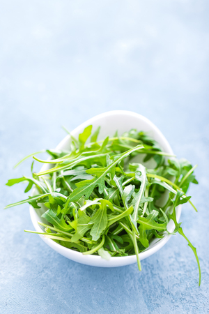 Fresh arugula leaves in bowl on table. Light background, closeup