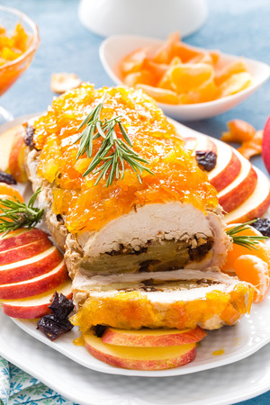 Baked meatloaf stuffed with apples and plums, decorated tangerine confiture. Christmas menu