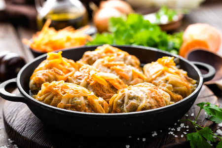Cabbage rolls stewed with meat and vegetables in pan on dark wooden background Фото со стока