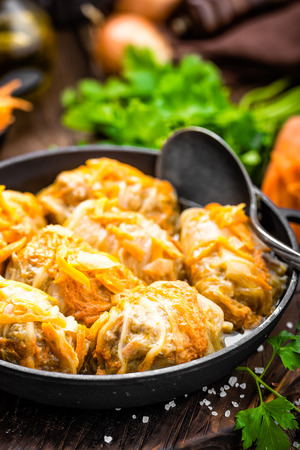 キャベツロールは、暗い木製の背景に鍋に肉と野菜で煮込み