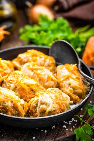 Koolbroodjes met vlees en groenten in pan op donkere houten achtergrond worden gestoofd die Stockfoto