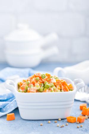 Guisantes verdes guisados con zanahorias en salsa cremosa de leche blanca, guiso de verduras Foto de archivo - 93882639