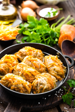 Cabbage rolls stewed with meat and vegetables in pan on dark wooden background Stock Photo - 93746703