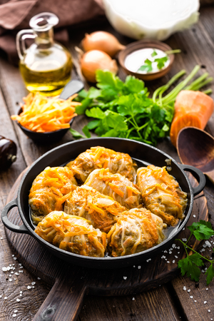 Cabbage rolls stewed with meat and vegetables in pan on dark wooden background Banco de Imagens