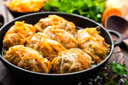 Cabbage rolls stewed with meat and vegetables in pan on dark wooden background Stock Photo
