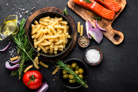 Pasta, salmon fish and ingredients for cooking on black background, top view. Italian food Stock Photo