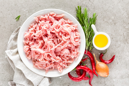 Mince. Ground meat with ingredients for cooking on light grey background. Top view 免版税图像