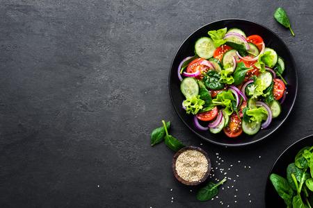 Gesunder Gemüsesalat der frischen Tomate, der Gurke, der Zwiebel, des Spinats, des Kopfsalates und des indischen Sesams auf Platte. Diät-Menü. Ansicht von oben. Standard-Bild
