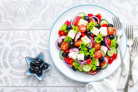 Greek salad of fresh cucumber, tomato, sweet pepper, lettuce, red onion, feta cheese and olives with olive oil. Healthy vegetarian food