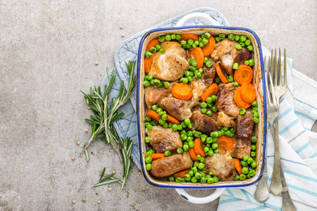 Meat baked with carrot and green peas Stock Photo