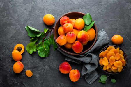 Fresh apricots with leaves and dried in bowl on table
