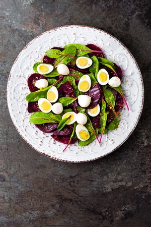 Fresh vegetable salad with boiled beet, mangold leaves, walnuts and quail eggs