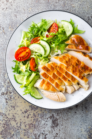 Chicken breast or fillet, poultry meat grilled and fresh vegetable salad of tomato, cucumber and lettuce. Healthy diet menu for lunch