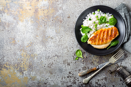 Chicken breast or fillet, poultry meat grilled and boiled white rice with green peas and fresh spinach leaves. Healthy diet menu for lunch Zdjęcie Seryjne