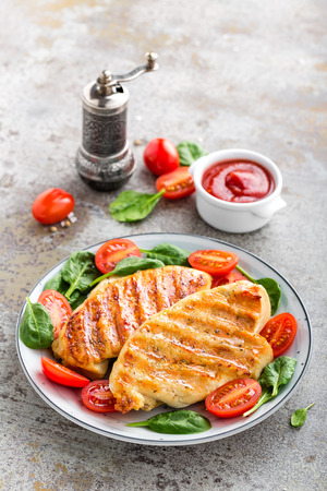 Chicken breast or fillet, poultry meat grilled and fresh vegetable salad of tomato and spinach. Healthy diet menu for lunch